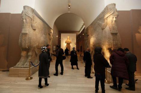 Visitantes al Museo Nacional de Irak observan algunas de las piezas que sobrevivieron al saqueo de 2003 / Reuters (El País)
